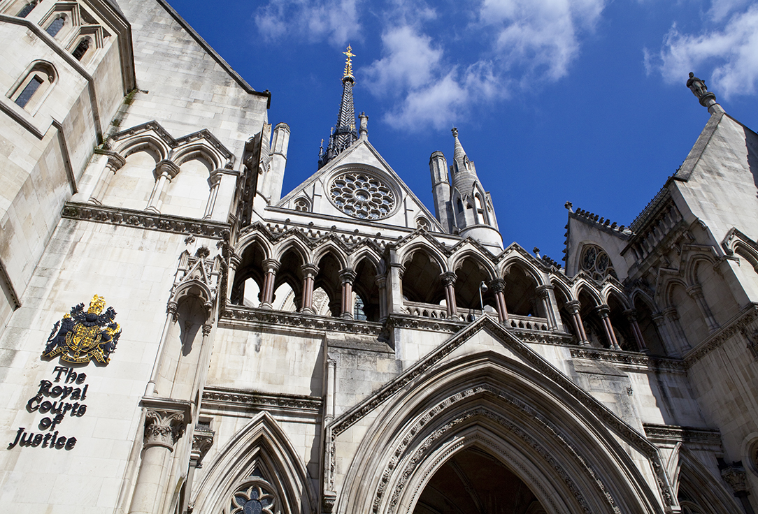 Daytime close up of the Royal Courts of Justice beneath blue skies