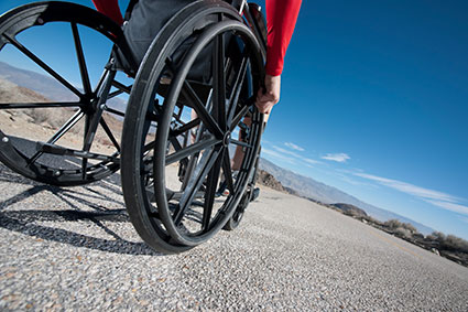 Spinally injured person in a wheelchair with the horizon in the distance